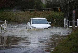 A car drives along a flooded road in the village of Great Easton, Dunmow, Essex (Yui Mok/PA)