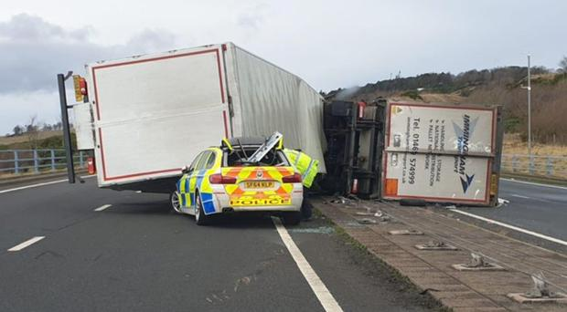 The police car was partially crushed by the lorry (Police Scotland/PA)