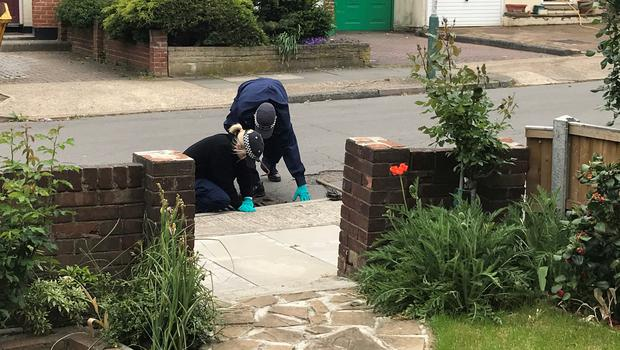 Police officxers searching drains in Ashmour Gardens, Romford, east London, where an 85-year-old woman has been found dead (Thomas Hornall/PA)