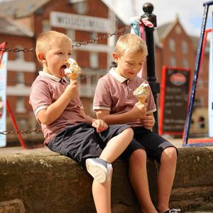 Max, aged four, and brother Oliver Woodhouse, aged six, eat ice creams by the River Ouse in North Yorkshire