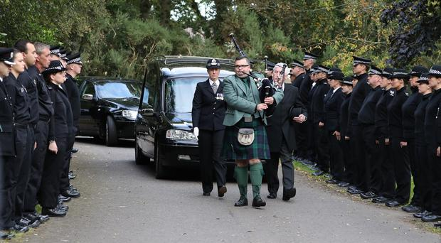 Police officers and other emergency services staff form a guard of honour as the hearse carrying the coffin of PC Roy Buggins arrives at Parkgrove Crematorium, Friockheim (Andrew Milligan/PA)