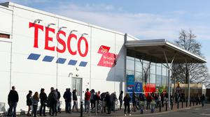 People queue outside a Tesco Extra store (PA)