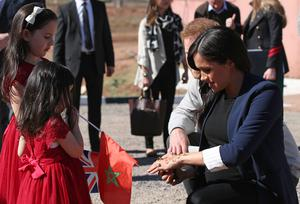 The Duchess of Sussex shows two girls her henna design (Yui Mok/PA)