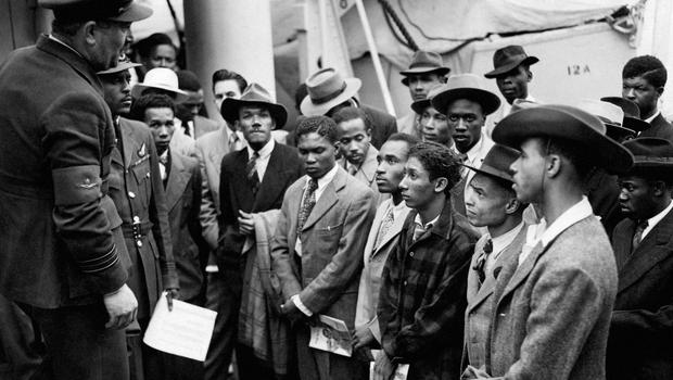 Jamaican immigrants welcomed by RAF officials in 1948 after arriving on the HMT Empire Windrush (PA)