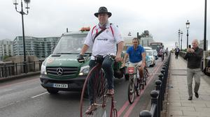 Alan Price cycles across Battersea Bridge (Anthony Devlin/PA)