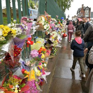 People leave flowers at the scene of the murder at the junction of Artillery Place and John Wilson Street in Woolwich