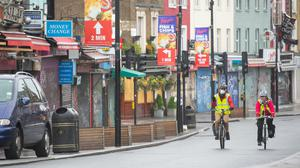 Cyclists ride past shuttered shops on Camden High Street in north London (Dominic Lipinski/PA)