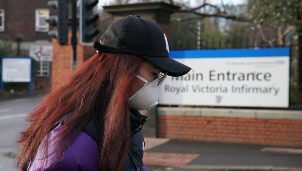 A woman wears a mask outside Newcastle's Royal Victoria Infirmary amid the coronavirus outbreak across the world (Owen Humphreys/PA)