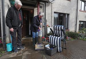 Jean Hendrie and William Craik cleaning their house in Pyothall Court in Broxburn after flooding (Andrew Milligan/PA)