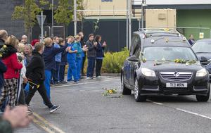 Colleagues threw flowers on to the hearse as it passed the hospital where Ms Murphy worked (Jane Barlow/PA)