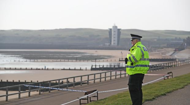 A policeman stands by a cordon at Aberdeen Esplanade following the death of two women who were pulled from the water (Jane Barlow/PA)