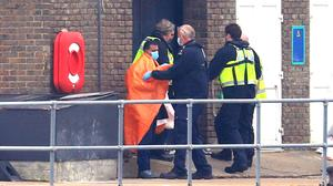 A man thought to be a migrant is assessed by a Border Force officer after being brought into Dover (Gareth Fuller/PA)