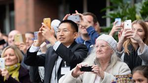 Members of the public take pictures of Prince Harry leaving Nottingham's new Central Police Station during a day of visits to the city focused on young people and communities.