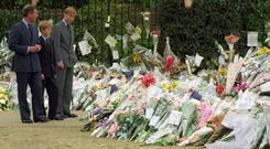 The Prince of Wales and his sons Prince William (r) and Prince Harry view the floral tributes to their mother, Diana, Princess of Wales, at Kensington Palace (Rebecca Naden/PA)