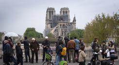 People walk past the Notre Dame Cathedral in Paris (Victoria Jones/PA)