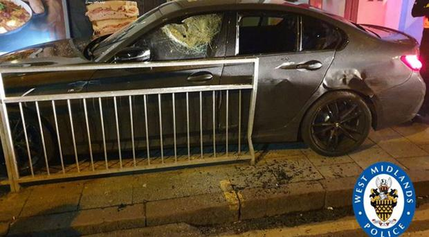 The BMW was pinned between a wall and railings (West Midlands Police/PA)