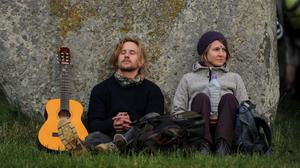 Members of the public rest against one of the stones at Stonehenge in Wiltshire