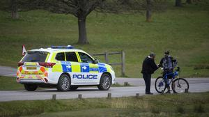 A police patrol stops to speak to a cyclist in Richmond Park, south-west London, during the coronavirus lockdown (PA)