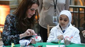 The Duchess of Cambridge makes a dinosaur egg whilst attending a children's tea party with pupils from Oakington Manor Primary School in Wembley, at the Natural History Museum in London.