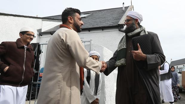 Aihtsham Rashid (centre left) greets Iman Mufti Abdur Rahman Mangera in Stornoway as they attend the official opening of the first mosque in the Outer Hebrides (Andrew Milligan/PA)