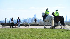 Mounted police officers speak to people on Primrose Hill, London, as the UK continues in lockdown to help curb the spread of the coronavirus (Kirsty O'Connor/PA)