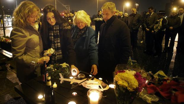 Members of the public light candles around a model of a police helicopter before the minute's