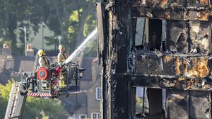 Fire service personnel survey the damage at Grenfell Tower (Rick Findler/PA)