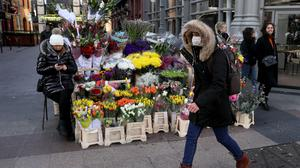 A man wearing a mask to protect against the spread of coronavirus walks past flower sellers (Brian Lawless/PA)