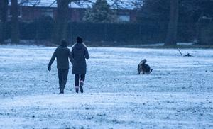 People walk their dog through the snow in Woolton, Liverpool (Peter Byrne/PA)