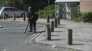 A volunteer cleans up in Overton Road (Jonathan Brady/PA)
