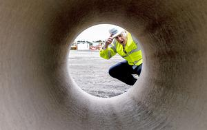 Prime Minister Boris Johnson looks through a large bore pipe during a visit to the Siemens Rail factory construction site in Goole (Peter Byrne/PA)
