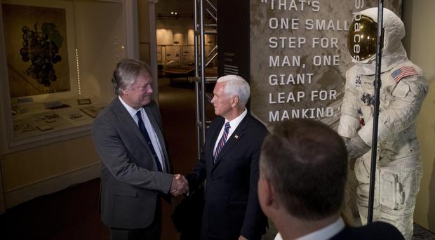 Rick Armstrong, the son of Neil Armstrong, left, and Vice President Mike Pence, right, shake hands after unveiling Neil Armstrong's Apollo 11 spacesuit at the Smithsonian's National Air and Space Museum on the National Mall in Washington, Tuesday, July 16, 2019. (AP Photo/Andrew Harnikl)