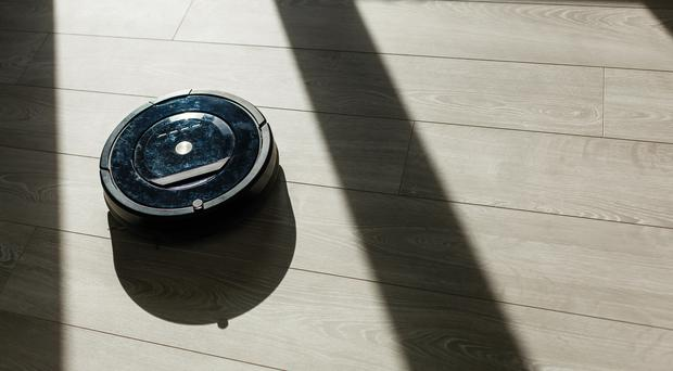 A robot vacuum cleaner on a laminate wood floor(Sinenkiy/Getty/PA)