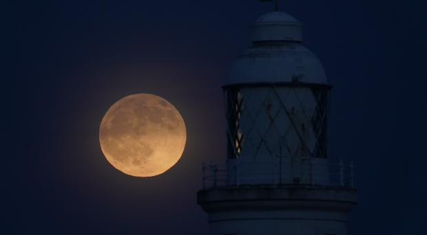 A view of the 'wolf moon', the first full moon of 2020, over St Mary's Lighthouse at Whitley Bay in Northumberland (Owen Humphreys/PA)
