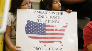 Two girls hold up a sign in favour of DACA
