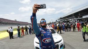 Driver Bubba Wallace takes a selfie with himself and other drivers that pushed his car to the front in the pits of the Talladega Superspeedway (John Bazemore/AP)