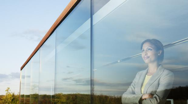 A woman looks out of a window thinking (Martin Barraud/Getty Images)
