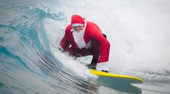 A surfer gets into the festive spirit dressed as Santa at an inland surfing lagoon (Ben Birchall/PA)