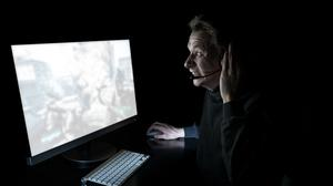 Young man playing computer games in dark room