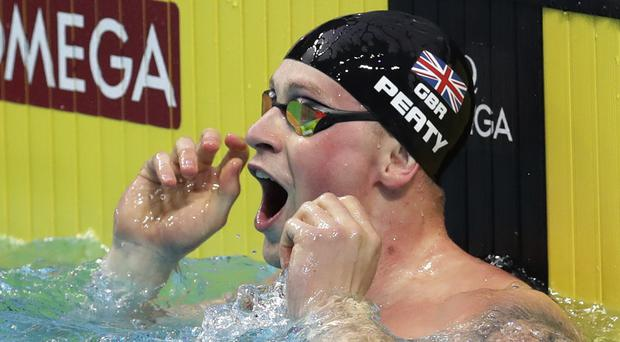 Adam Peaty celebrates breaking a world record – (Michael Sohn/AP)