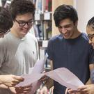 A-level students read their exam results (Victoria Jones/PA)