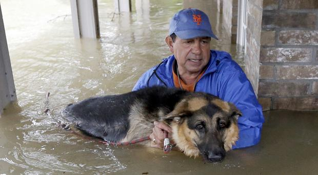 Joe Garcia and his dog Heidi were rescued after floodwaters rose (David J. Phillip/AP/PA)