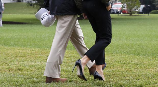 The Trumps walk on the lawn outside the White House to the helicopter
