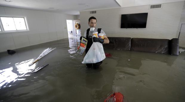 Gatson Kirby walking through floodwaters waist high in his home in the aftermath of Hurricane Harvey