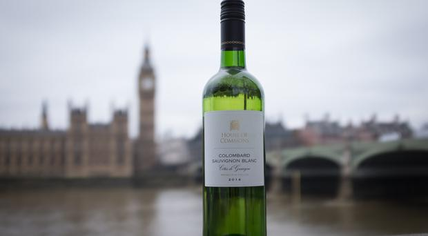 A bottle of House of Commons Colombard Sauvignon Blanc wine is seen in front of the Houses of Parliament