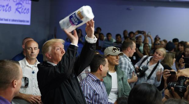 President Donald Trump tosses paper towels into a crowd as he hands out supplies