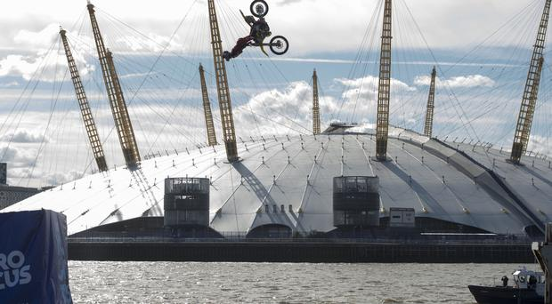 Nitro Circus ringleader and American professional motorsports competitor and stunt rider Travis Pastrana performs back-flips on a motorcycle between two floating barges in the River Thames