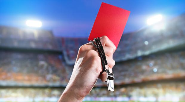 The hand of a referee with a red card and a whistle