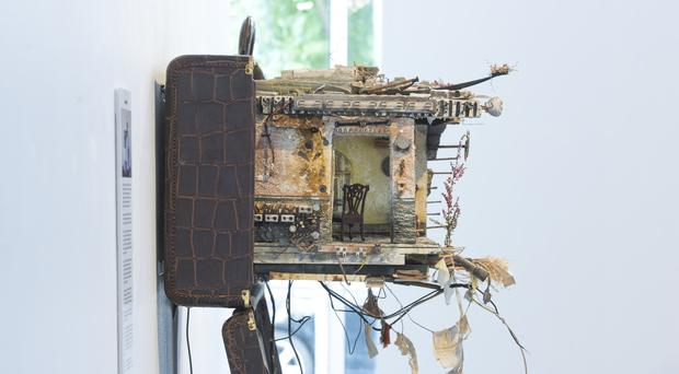 A suitcase with a home in it built by Mohamed Hafez