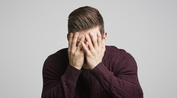 A man covering his face with his hands